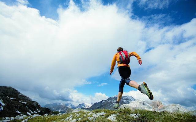Woman trail running under cloudy skies