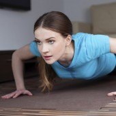 Beautiful young woman doing push-ups at home